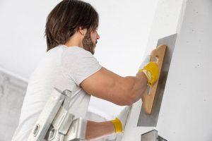 man plastering walls