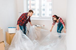 couple laying down plastic sheeting
